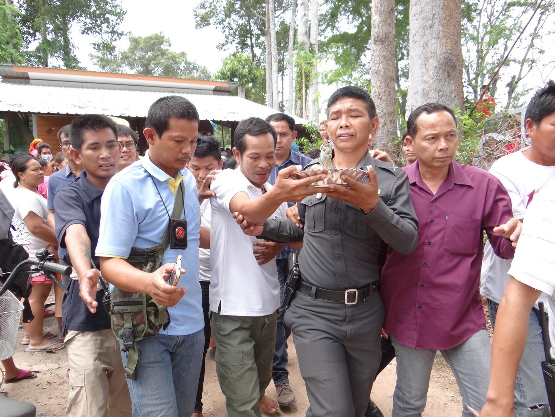 Policie, obklopená davem poutníků přenáší Nágu do Policejního vozu