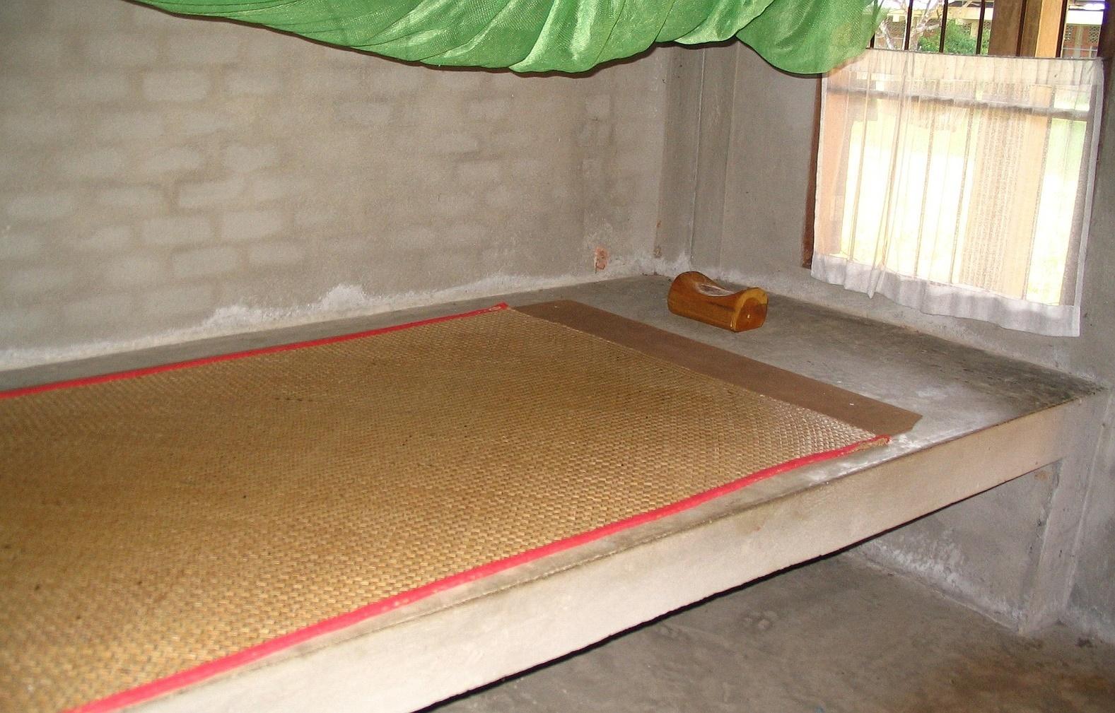 Betonová postel, rohož, moskytiéra a dřevěný polštářek - Wat Suan Mokkh - Thajsko