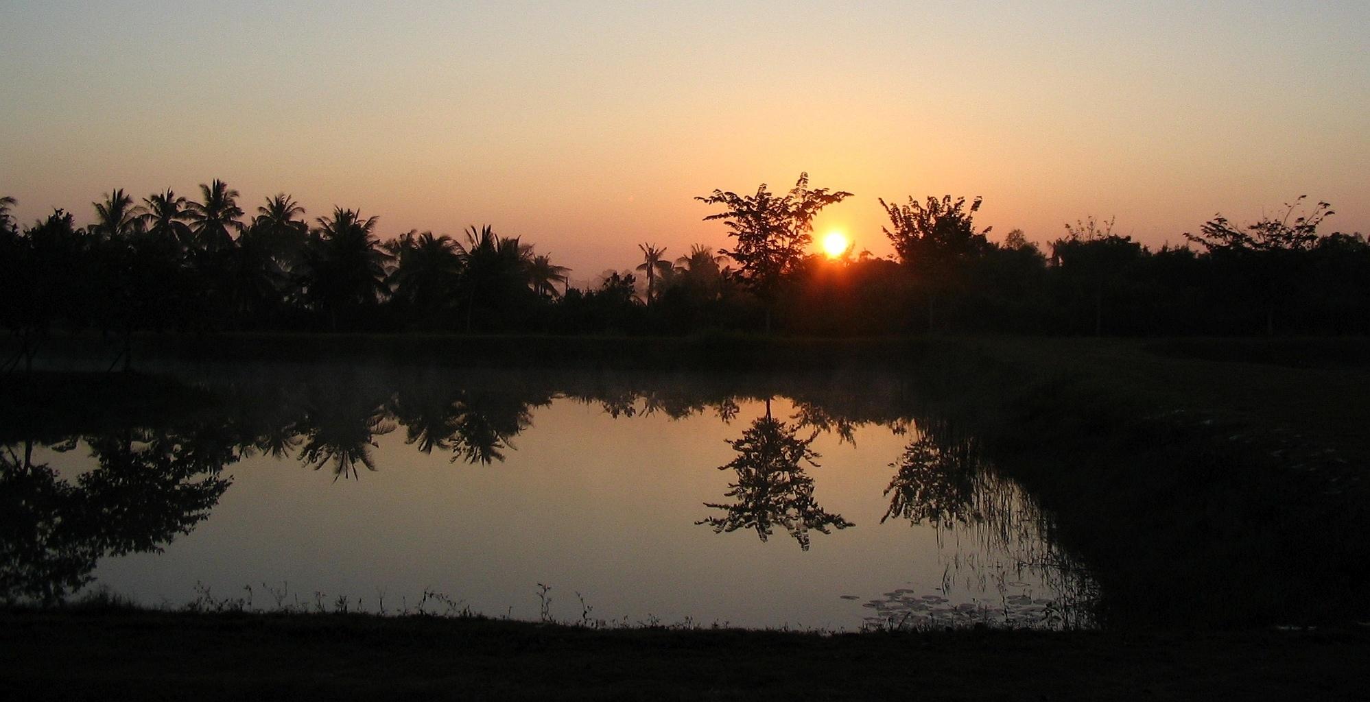 Pohled z meditační haly na výhod slunce - Wat Suan Mokkh - Thajsko
