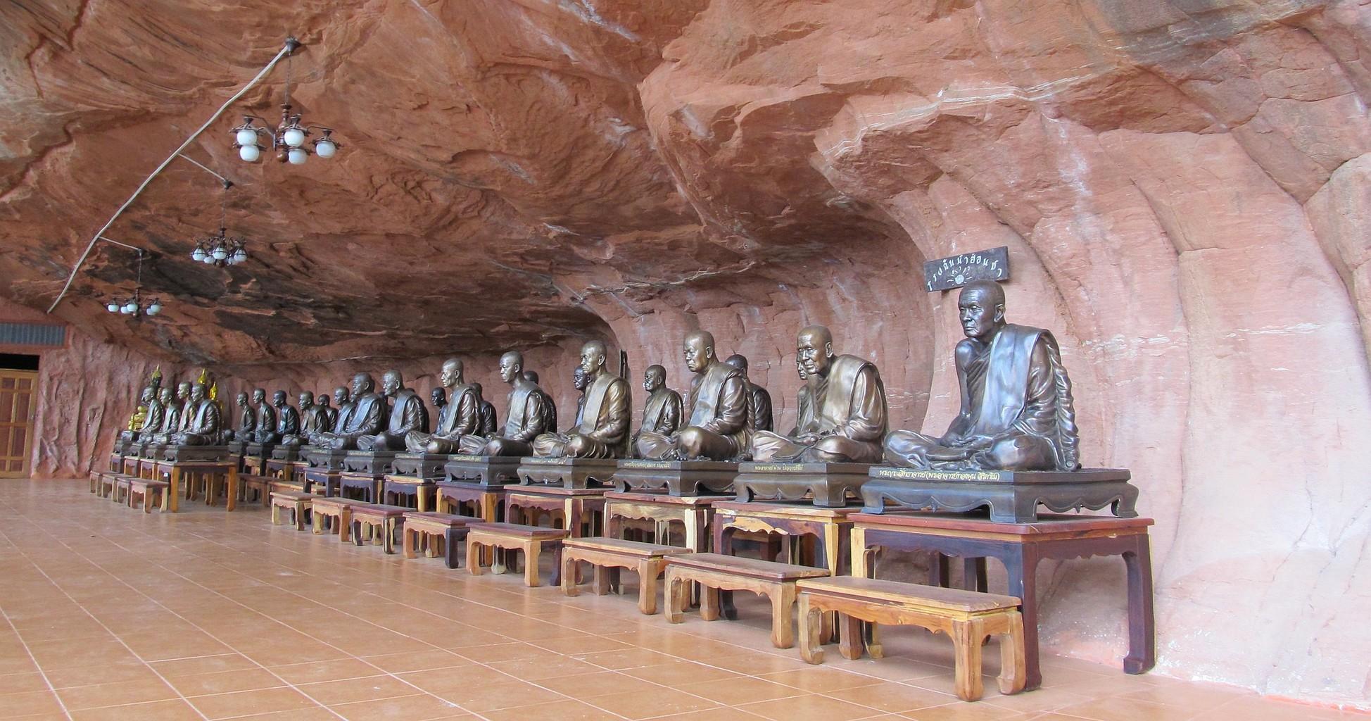 Bronzové sochy arahatů pod skalním převisem Wat Phu Thok - Bueng Kan