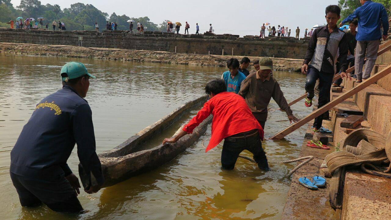 Dělníci přemisťují osm set let starý člun do vodní nádrže obklopující Angkor Wat